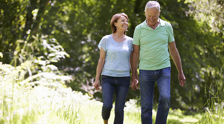 An older couple holds hands while walking outdoors