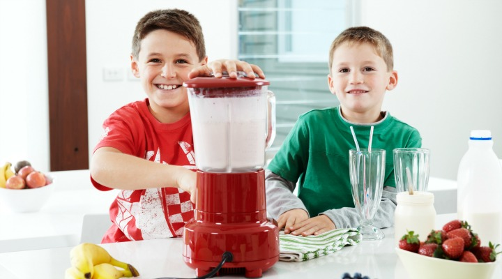 Two boys make healthy smoothies in the kitchen