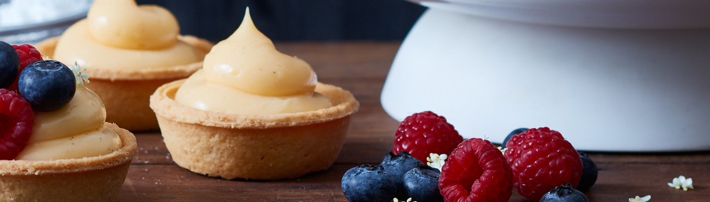 A picture of a selection of custard filled tarts, served with raspberries and blueberries.